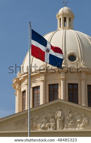 The flag of the Dominican Republic and the dome of the National Palace in the capital city, Santo Domingo. - stock photo