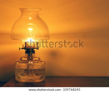 The flame of an old oil lamp casts a soft glow