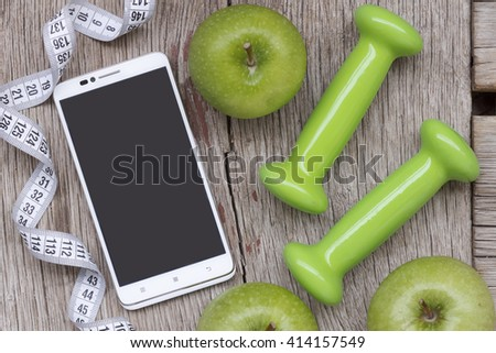 The flat position, White smart-phone ripe green apple, dumbbells and measuring tape on a gray wooden background. Concept: the fashion for a healthy lifestyle  - stock photo