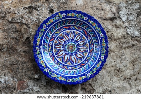 The floral decorative plate on a wall background - stock photo