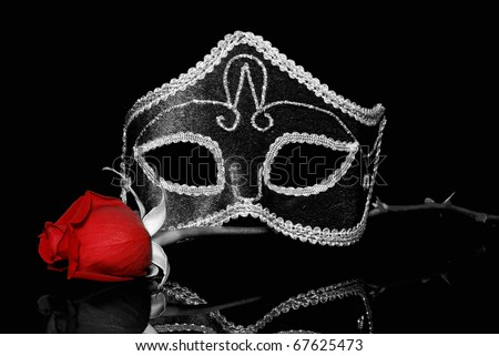 The flower and Venetian mask  on a black background - stock photo