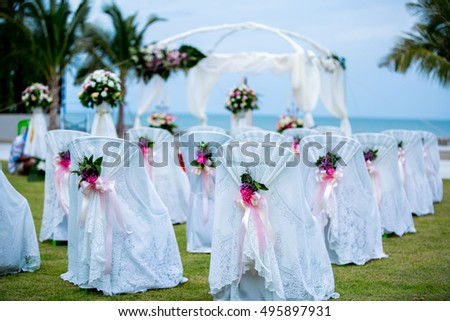 the flower decorated chairs in outdoor wedding ceremony