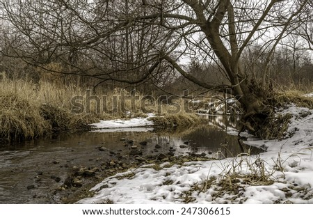 The flowing creek with light snow in Midwest. - stock photo