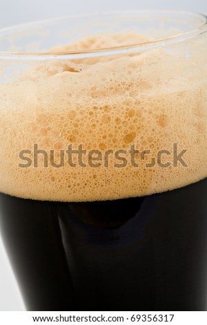 The foam head on stout beer - stock photo