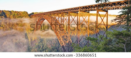 The fog still lifting off the New River below the New River Gorge Span Bridge in the Autumn sunrise.