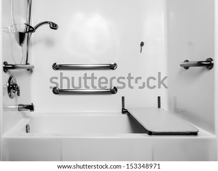 The fold down seat helps disabled and handicap use the shower with access at the height of a wheelchair. The adjustable shower handle allows multiple heights for use. Wall handles help accessibility.  - stock photo