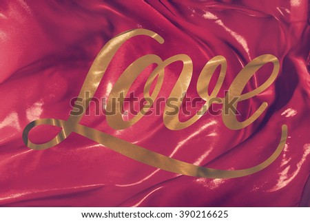 The folds of red silk fabric fluttering in the wind with inscription Love - stock photo