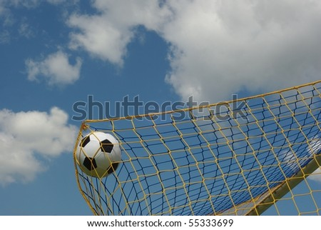 the foot ball in mesh of goal on background of clouds - stock photo
