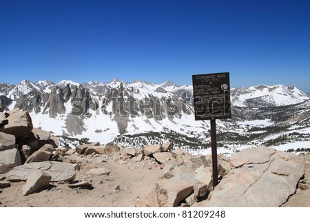 the 11760 foot Kearsarge Pass over the Sierra Nevada into Kings Canyon National Park in California with sign - stock photo