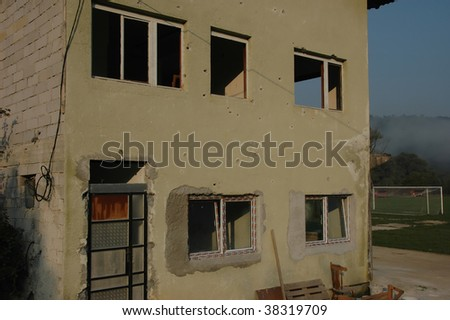 The football stadium guesthouse being restored with new windows following the war in Bosnia. It was attacked by serbian troops coming from neighbouring serbian village. Bullet holes cover the walls. - stock photo