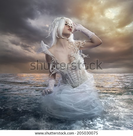 the forces of nature, blonde woman on the rocks with the sea raging and powerful - stock photo