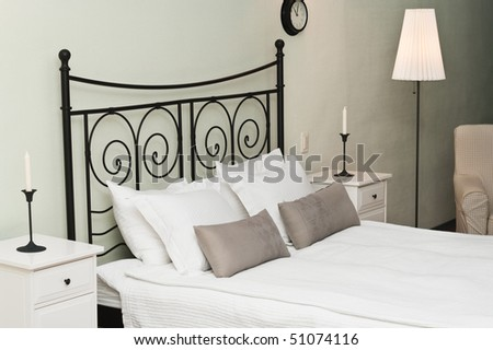 The forged bed with pillows and a white coverlet. Candles in a room interior, a bedroom