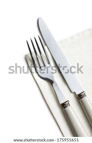 the fork and knife on white napkin