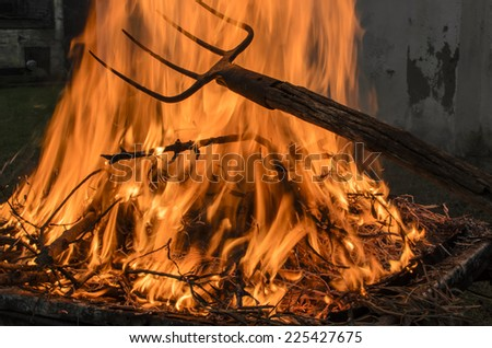 The fork moves the wood burning with high flames. - stock photo