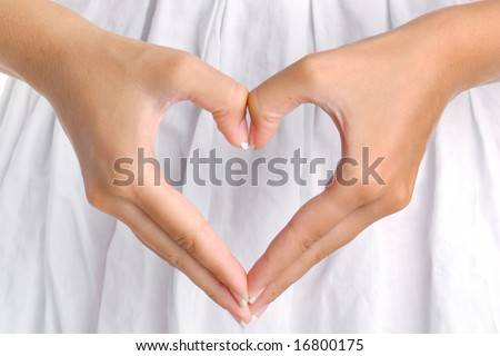 The form of heart shaped by female hands on a white dress background. - stock photo