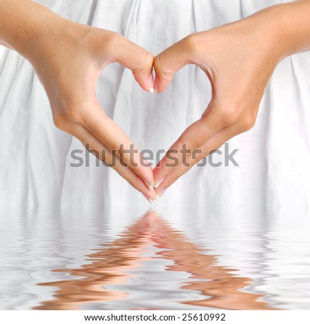 The form of heart shaped by female hands on a white dress background with water reflection. - stock photo