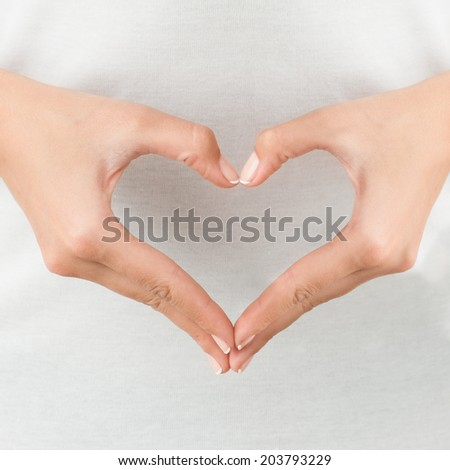The form of heart shaped by female hands on body background isolated on white. - stock photo