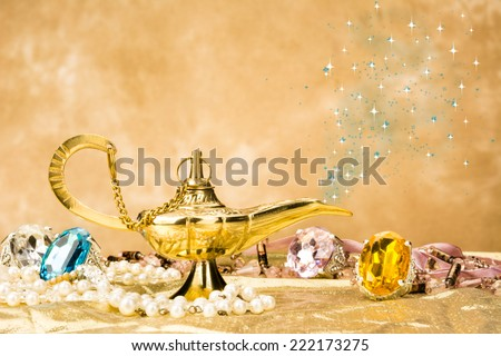 The formation of a magical deity from a gold, magic lamp surrounded by a wealth of jewelry and fantasy. - stock photo