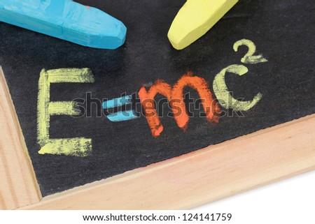 The formula E=mc2 on a blackboard at school - stock photo