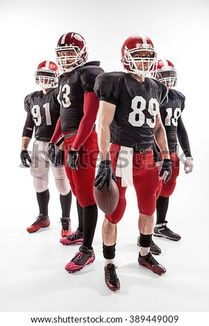 The four american football players posing with ball on white background - stock photo