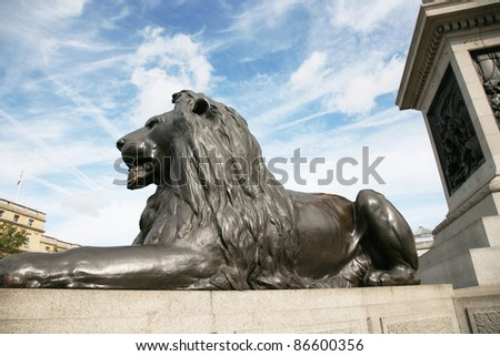 The four lion statues surrounding Nelson's column in Trafalgar Square are one of the most famous places for tourists. - stock photo