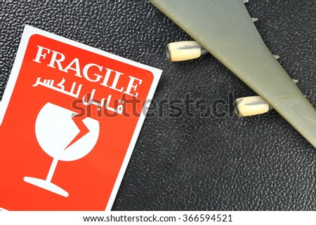 The fragile paper sticker label put beside the plastic jet plane wing model represent the logistic business and symbol concept related idea. - stock photo