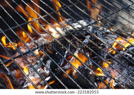 the fragment of grill with flames - stock photo