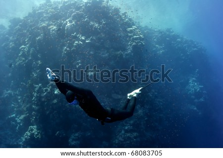 The freediver moves underwater near the coral reef at the depth of Blue Hole. Read Sea, Egypt. - stock photo