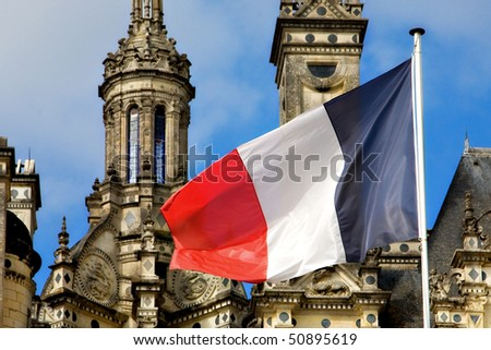 The French flag waves dramatically in front of the ornate towers of the Chateau at Chambord. - stock photo