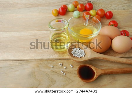 The fresh eggs nailed and tomatoes with vegetable oil in a glass container sauce and pepper seed in a ladle, placed on a wooden background. - stock photo