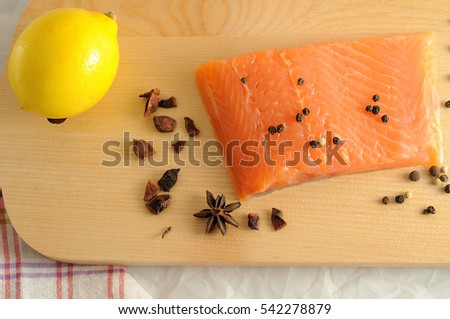 The fresh fish with cloves, pepper and lemon on a wooden board,cooking concept
