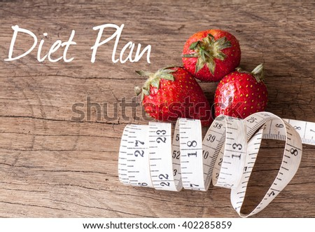 The fresh Strawberry with Measuring tape on wood background in concept of healthy and diet - stock photo