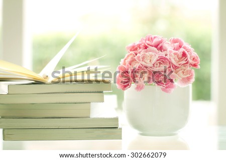 the fresh sweet and romantic pink carnation flower with books background , reading for relaxing and romance moment  - stock photo