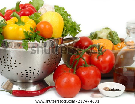 The fresh washed-up vegetables in a colander on a white background.