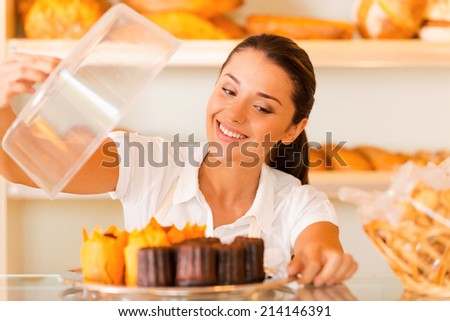 The freshest bakery for our customers. Beautiful young woman in apron carrying plate with fresh cookies and smiling while standing in bakery shop - stock photo