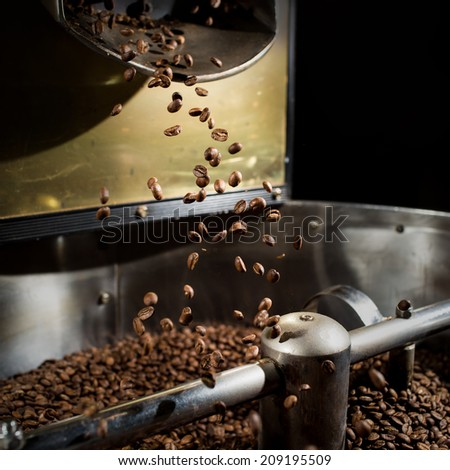 The freshly roasted coffee beans from a coffee roaster being poured into the cooling cylinder. Frozen moment. - stock photo