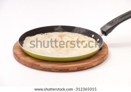 The fried pancake in a frying pan over white background. - stock photo