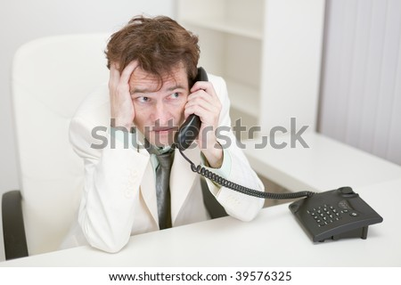 The frightened guy speaks by phone at office