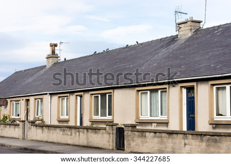 The front aspect of a row of stone bungalows in Lossiemouth, Scotland - stock photo