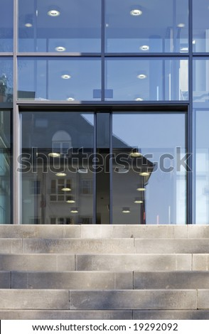 The front door of a office block, reflecting  buildings in the glass - stock photo