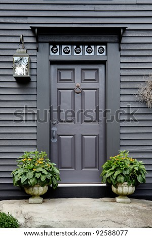 The front door on an authentic colonial style reproduction home.  This image depict the bullet glass over the door, and reproduction siding and lights.