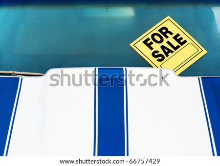 The front end of a car 'for sale' with a sign parked on a front yard. - stock photo
