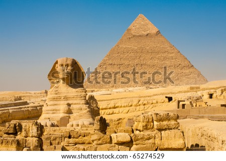 The front face and body of the Sphinx and the biggest Great Pyramid of Khafre appear side by side in the desert of Giza, Cairo, Egypt. Horizontal Copy Space - stock photo