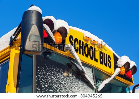 The front of a school bus after a fresh winter snowfall. - stock photo