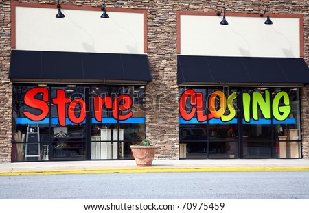 """The front of a store that is going out of business. The words """"Store Closing"""" are painted on the windows. - stock photo"""