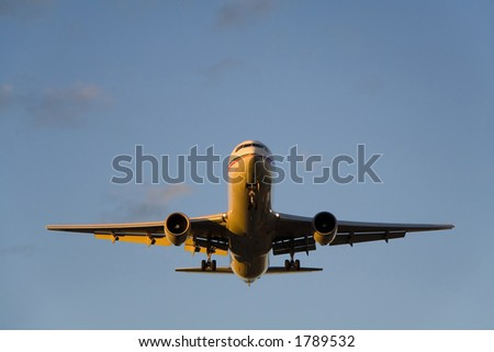 The front of an Airbus A310 nicely illuminated from the side by the setting sun. - stock photo