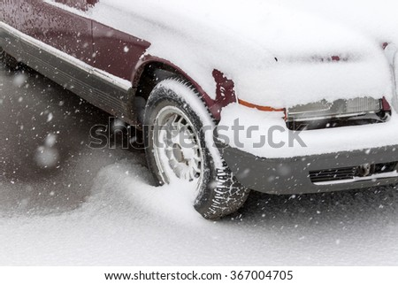 The front of the car - the bonnet, under a layer of snow - stock photo