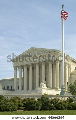 The front of the US Supreme Court in Washington, DC. American flag on a mast in foreground. - stock photo