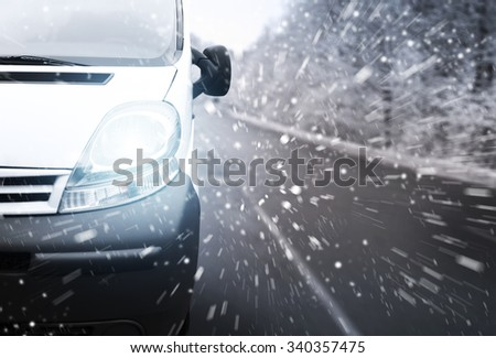The front part of white minivan on the road background with snowstorm - stock photo