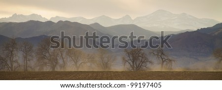 The front range foothills of the Colorado Rocky Mountains above Boulder with haze in the air from the wildfires.  Also dust kicked up from a tractor plowing the farm fields. - stock photo